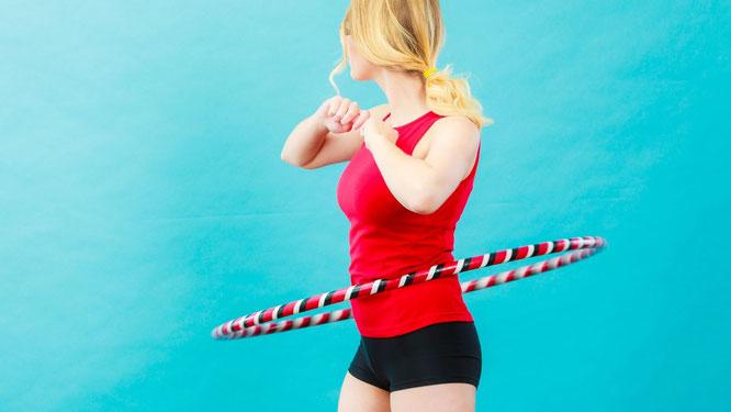 Frau schwingt Hula-Hoop-Reifen mit Gewicht