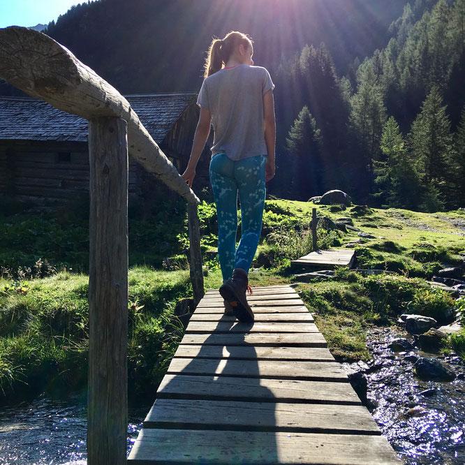 Mädchen geht auf einem Steg über einen Bergbach