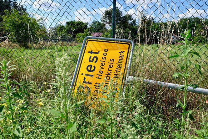 Ortsschild Briest umgefallen im Unkraut, Brandenburg