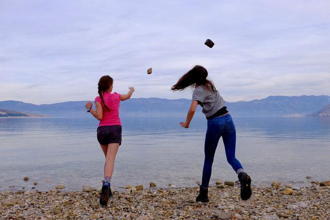 Krk Kroatien Mädchen werfen Steine ins Wasser