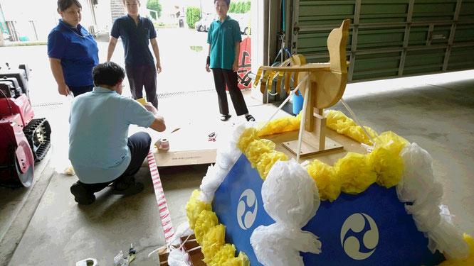 夕方の車庫内では、明日の夏祭りで使用されるお神輿が組み立てられていました
