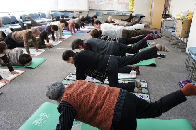 それぞれの力量・ペースで体を動かす参加者の皆さんと、いちばん辛い表情をしている訓練員(手前から6人目)