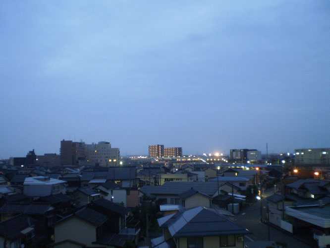 今日の夕刻の「イトーヨーカドー」屋上からの景色。梅雨空の下、肩を寄せ合う直江津の街並み