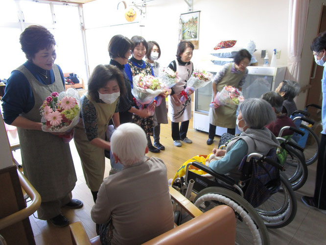 ご利用者さまからの花束の贈呈。突然のサプライズに喜んでいただいた「コスモス会」の皆さん