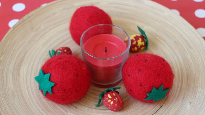 aus Walnüssen gebastelte Erdbeeren arrangiert mit Filzerdbeeren und Kerze