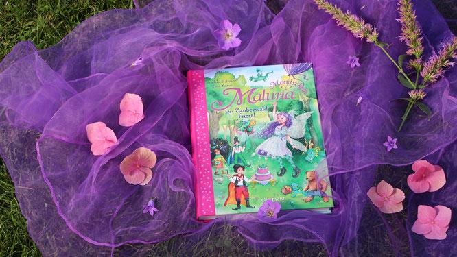 """Buch """"Maluna Mondschein - Der Zauberwald feiert!"""" mit Blüten und lila Seidentuch"""