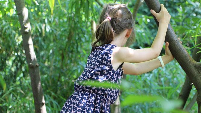 Unsere Große klettert auf einem Baum am Spielplatz im Palmengarten Frankfurt