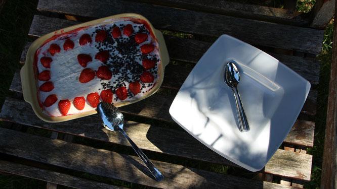 Das Erdbeer-Tiramisu wartet auf einer alten Gartenbank darauf verspeist zu werden