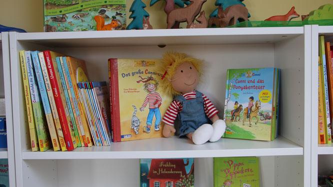 Conni-Puppe sitzt im Bücherregeal mit vielen Conni-Büchern