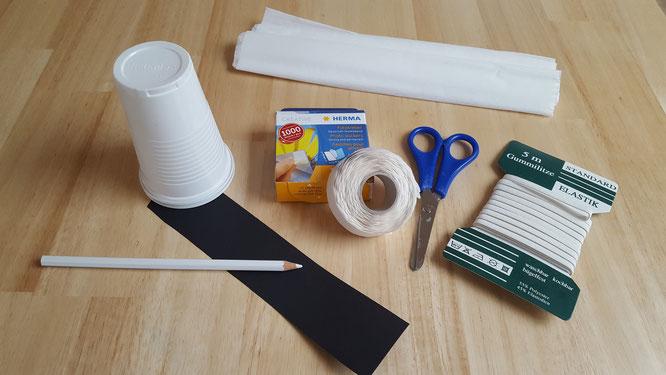 Das Material für ein Becher-Gespenst: Plastik-/Papp-Becher, Krepppapier, schwarzer Tonkarton, Gummiband