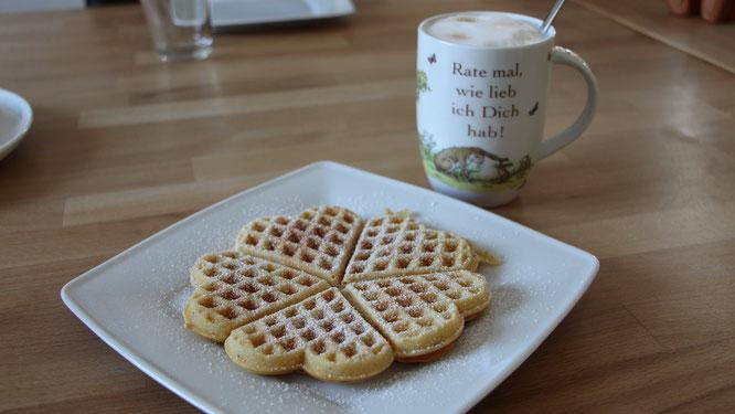 Eine Waffel mit Puderzucker auf einem Teller und dazu eine Tasse Kaffee