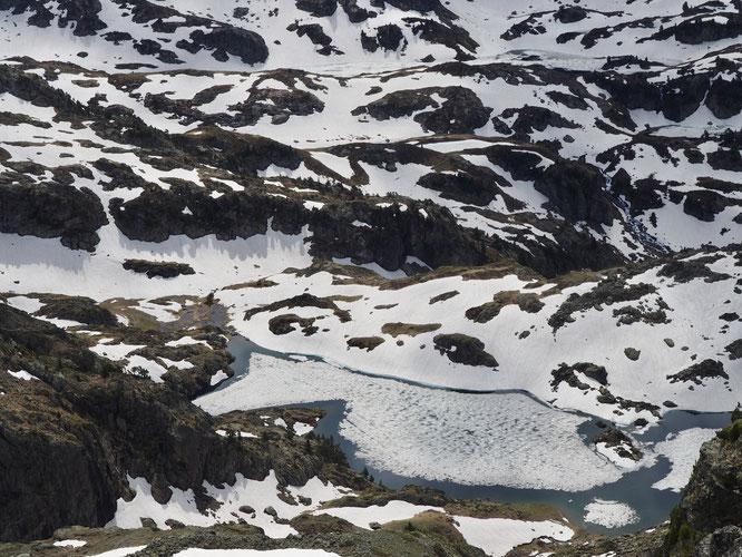 """En altitude c'est la période de la """"débâcle"""" pour les lacs de montagne. La glace résiste encore mais plus pour très longtemps. Ici, le lac Merlat vu depuis le sommet du Grand Colon."""