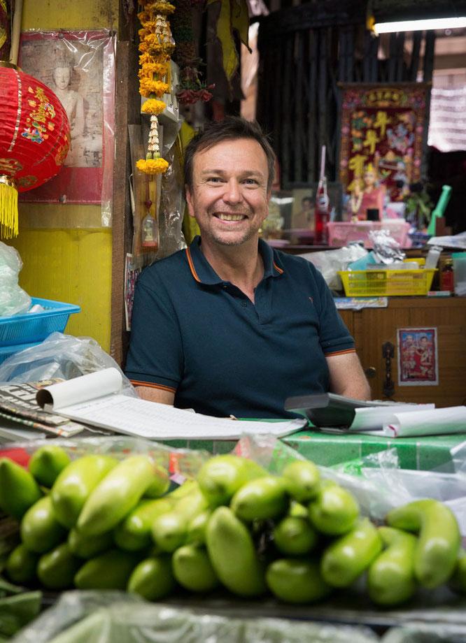 EIN GUT GELAUNTER DAVID THOMPSON, FOTOGRAFIERT AUF DEM MARKT IN MAHACHAI (FOTO: ENVER HIRSCH)