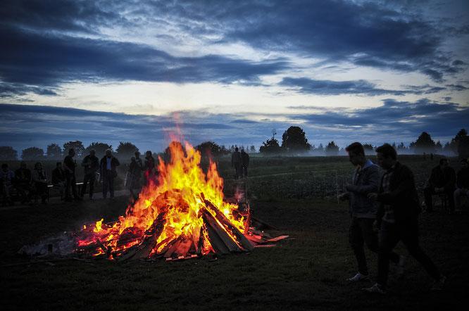 Das Sonnwendfeuer 2016, im Hintergrund die Abenddämmerung mit Wiesen und Bäumen im Nebel