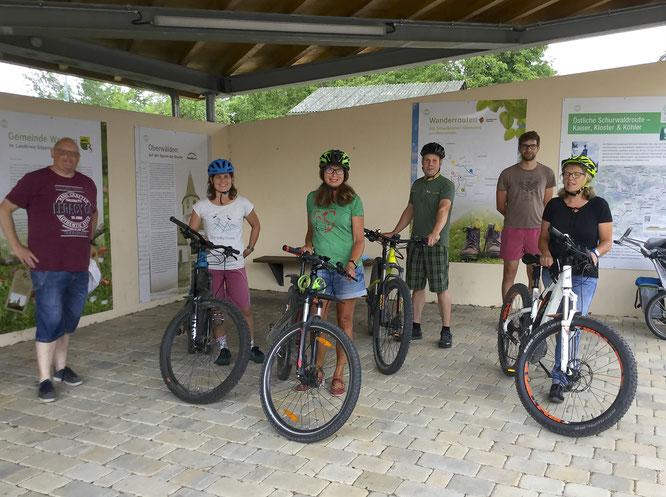 6 Personen und 4 Fahrräder stehen in Oberwälden am Pavillon