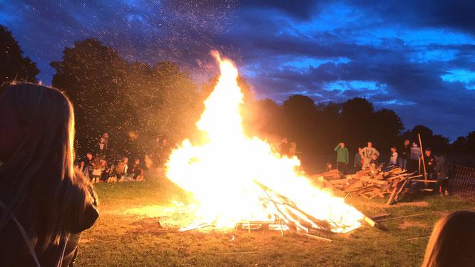 Feuer in der Abenddämmerung mit darum herum stehenden Leuten