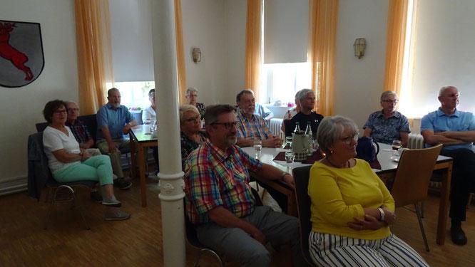 Bild: An quadratischen Tischen sitzen 14 Menschen und schauen in Richtung Leinwand.