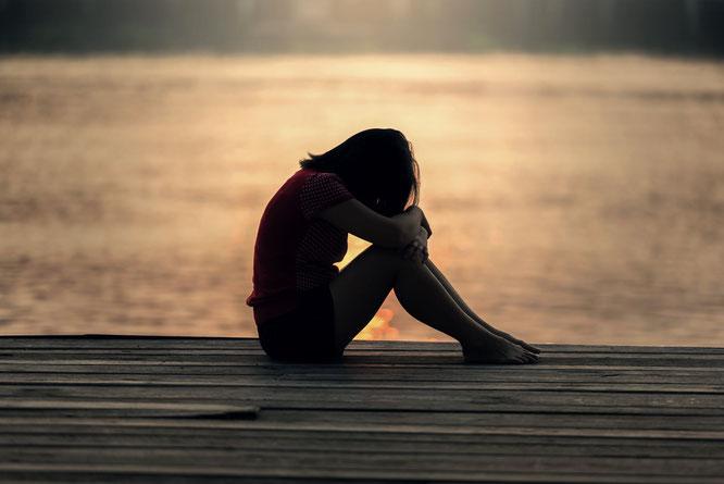 Frau sitzt alleine auf Steg bei See
