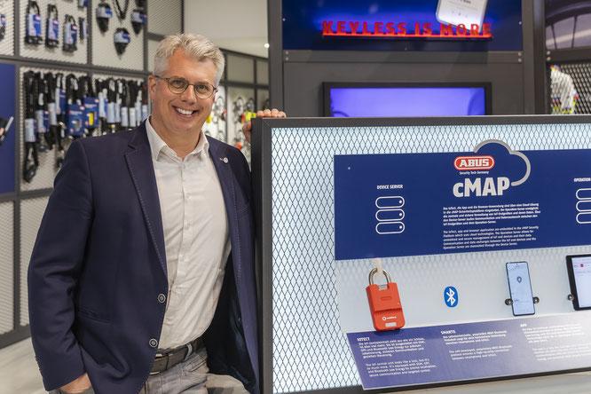"""Christian Rothe, Mitglied der Geschäftsführung bei ABUS, vor einem Infomodul, das die Funktionsweise von """"ABUS cMAP"""" – einem cloudbasierten Portal zur Administration und Steuerung digitaler Schlösser und deren Nutzer – demonstriert. © ABUS"""