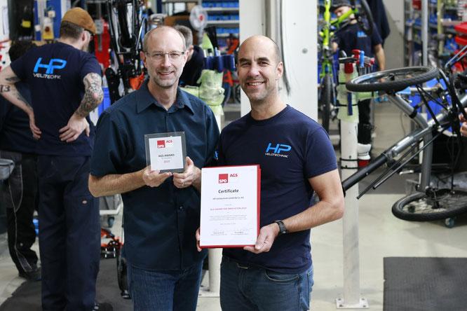 Paul Hollants und Daniel Pulvermüller mit Award und Urkunde in der Produktionshalle in Kriftel.