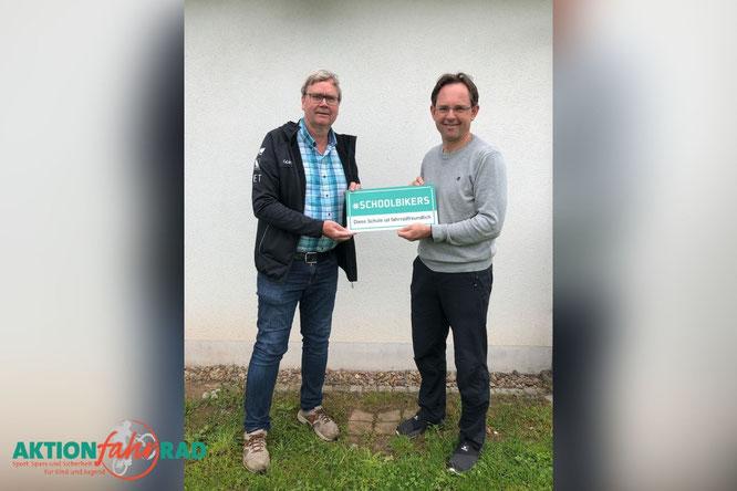 """Ulrich Fillies und Michael Kreil mit dem Schild  """"#SCHOOLBIKERS - Diese Schule ist fahrradfreundlich"""""""