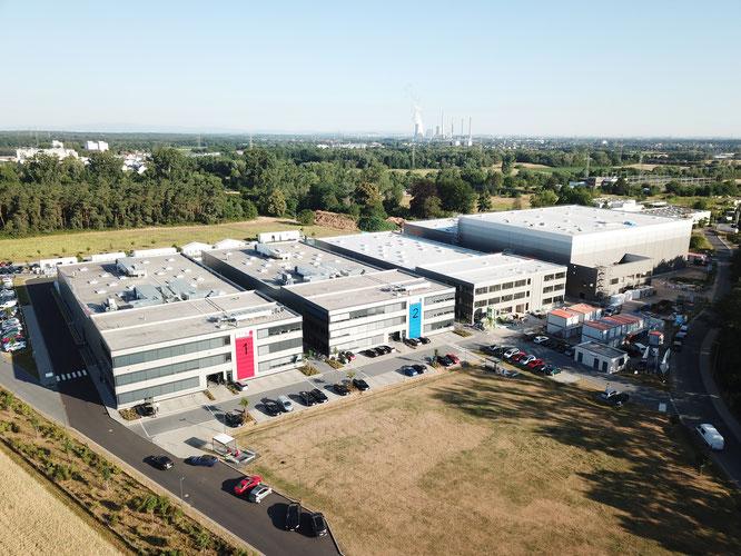 """Die Konzernzentrale der BMZ Group in Karlstein am Main, wo derzeit eine dritte Produktionshalle sowie das Logistik Center entstehen (1. und 2. Gebäude v. r.). In """"Unit 3"""" werden künftig die Batteriesysteme für das JV produziert."""