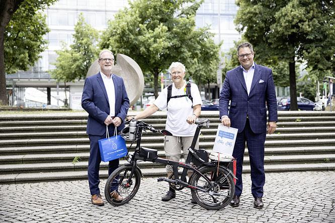 Patrick Döring (re., Vorstandsvorsitzender Wertgarantie) und Georg Düsener (Bereichsleiter Vertrieb Bike Wertgarantie) begrüßen Dr. Marta Binder bei ihrem Besuch in Hannover. Foto: S. Krahforst/Wertgarantie