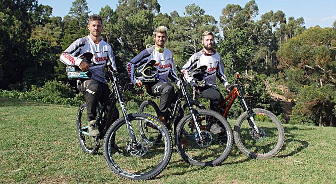 Die Downhill- und Freeride-Profis Clemens Kaudela (27, links), Sam Reynolds (26, Mitte) und Nicholi Rogatkin (22) setzen das Sonax Bike-Pflegeprogramm ab sofort im Rahmen internationaler Bike-Events in Szene.