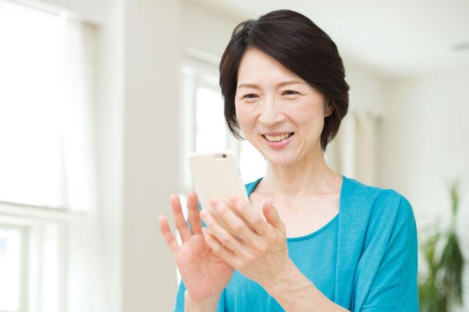 スマートフォンを笑顔で操作する女性