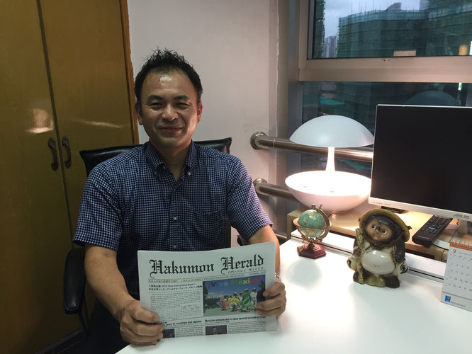 Tatsuya Ishigaki poses with a copy of Hakumon Herald in hand during an interview at his office in Shanghai.