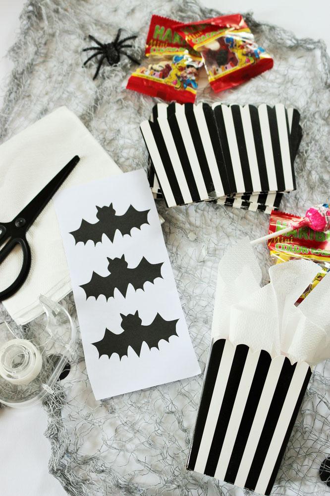 Bild: Eine schnelle last-minute Idee, um Halloween Süßigkeiten zu verpacken - in einer Papierbox samt Fledermaus Dekoration als Freebie Bastelvorlage, gefunden auf www.partystories.de