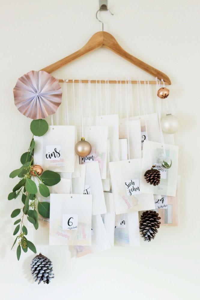 Bild: DIY Adventskalender Idee mit Kleiderbügel und Papiertüten, inklusive Freebie Zahlen zum ausdrucken im angesagten Lettering-Style; gefunden auf www.partystories.de