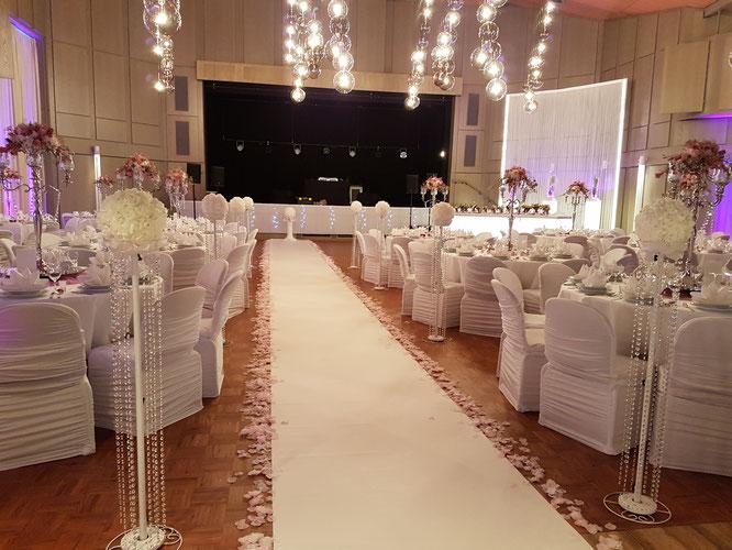 Eingang zum Saal im Kurhaus Potpourri Bad Fallingbostel mit rund dekorierten Gästetischen in rosa