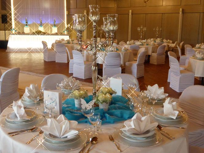 Winterhochzeit in blau mit künstlichem Schnee auf den Gästetischen, einem Kerzenständer und frischen Blumen