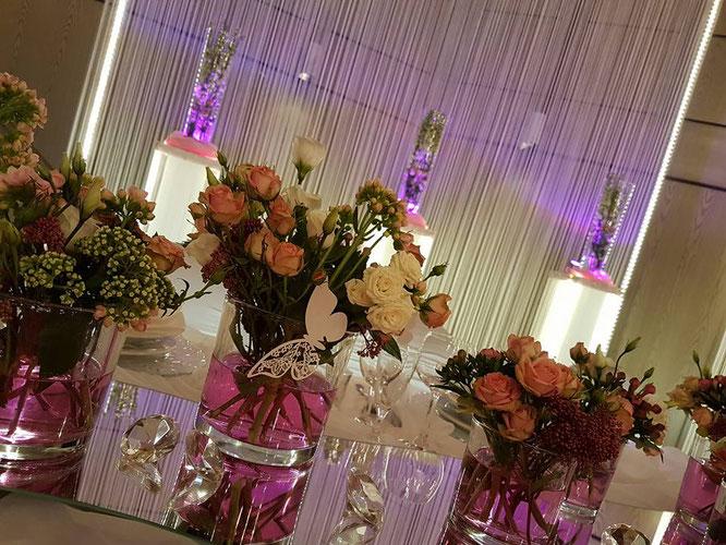 frische Blumen mit farbigem Wasser und Accessoires am Brautpaartisch