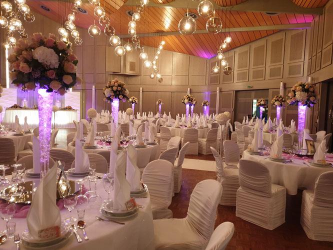extravagante Gästetische mit großem Blumengesteck und einer LED-beleuchteten Vase
