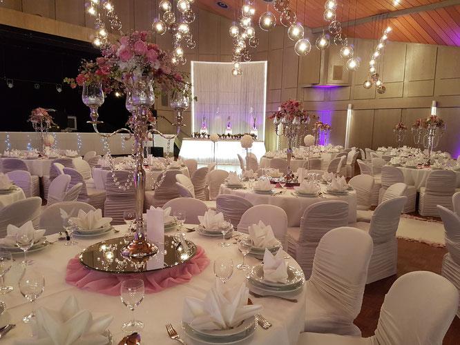 ein zartes Rosa für die Gästetische, romantischer Kerzenständer und farblich abgestimmten Blumen