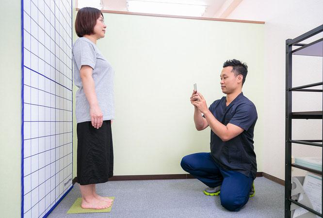 患者の姿勢をチェックする鍼灸師