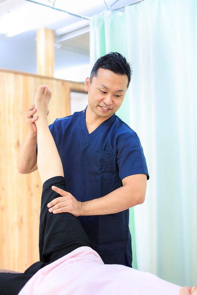 患者の下肢をストレッチする鍼灸師