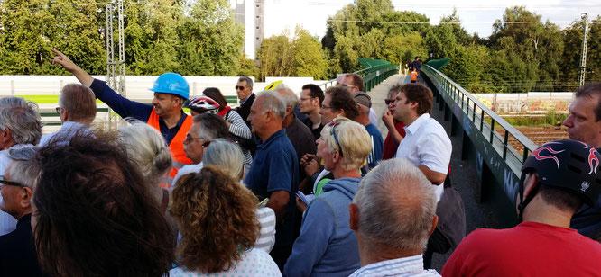 Auf der Brackstraßenbrücke lässt sich Michael Weinreich (MdHB) zusammen mit rund 50 Teilnehmern  die Baustelle vom Projektleiter Martin Steinkühler (DEGES) erklären