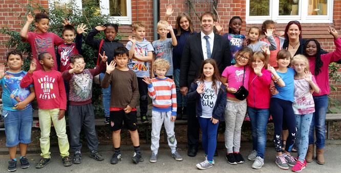 Bianca Neugebauer (Schulleiterin) und Michael Weinreich (MdHB)  unringt von Schulkindern der Katholischen Bonifatiusschule Wilhelmsburg
