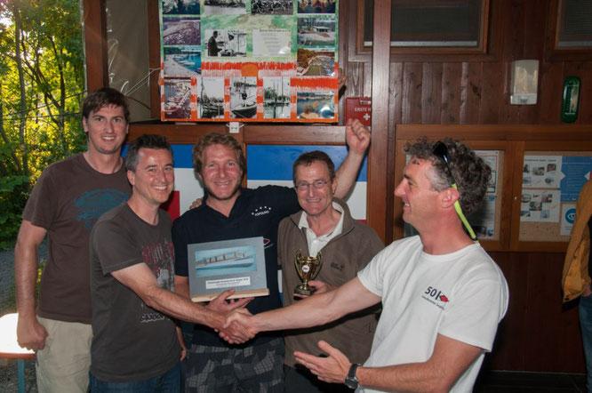Regattaleiter Andreas Duelli (rechts) beglückwünscht das Team um Norbert Brendle (2. von links). Sie sind die Clubmeister 2016 der Kressbronner Segler.