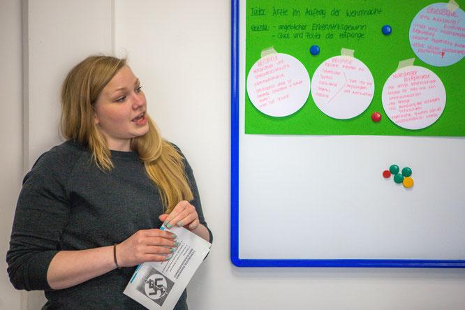 Teilnehmerin erklärt ein Plakat