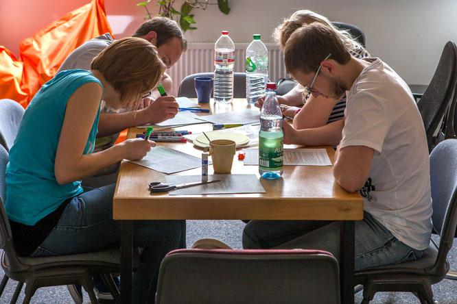 Vier Jugendliche sitzen am Tisch und bearbeiten Texte