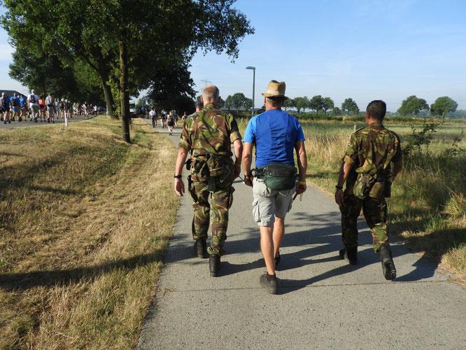 Un mal-voyant  emmené par des  amis . Une cordelette le relie au militaire sur  la gauche.