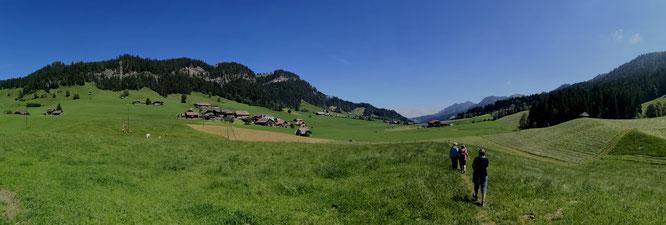 Wandern in schweizerischen Bergen über Felder, Hüel und vorbei an Bergdörfern
