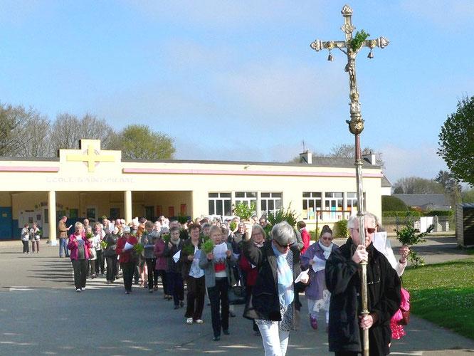 Après la bénédiction, les paroissiens sont invités à suivre la croix pour se rendre dans l'église, à l'image du peuple de Dieu qui marche dans la suite du Christ.