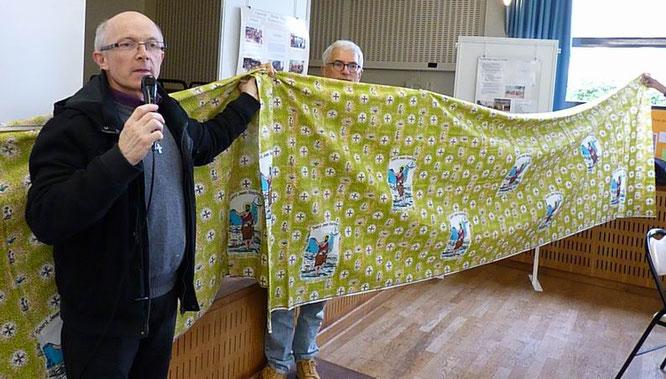 Yves laurent découvre le cadeau fait par la paroisse de Réo : une superbe nappe d'autel.
