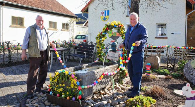 René Hagelberger (links) und Bernhard Peter vom Obst- und Gartenbauverein in Rilchingen-Hanweiler haben den Brunnen vor dem Bockstall österlich verziert.