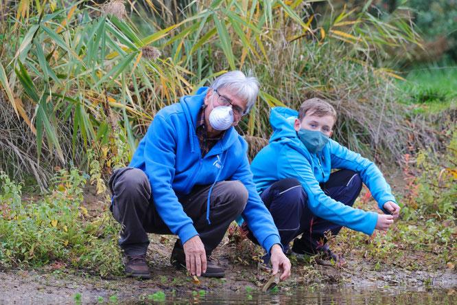 Axel Hagedorn zeigt Noah Dehnhart was es so alle im Teich gibt.